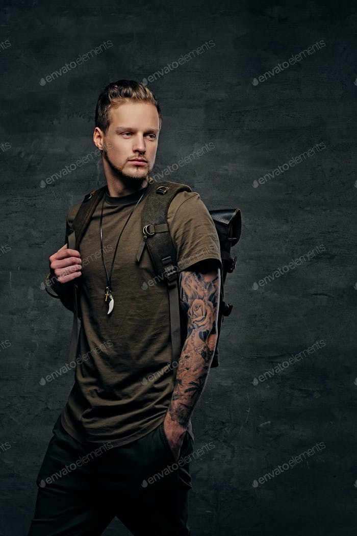 Backpacker in Camo green t shirt and tattoos on arms.