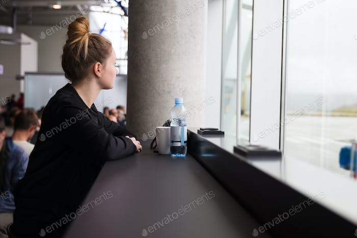 Traveling woman waiting at the airport and looking out the window