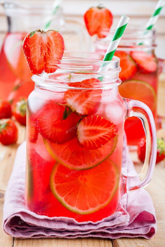 Erdbeerlimonade mit Limette und Eis im Mauerglas
