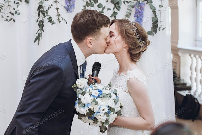 bride with microphone kissing with groom after toast at wedding reception