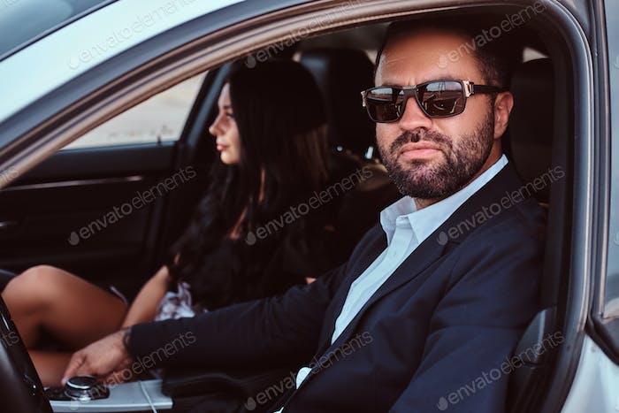 Красивая хорошо одетая пара сидит на передних сиденьях в роскошном автомобиле.