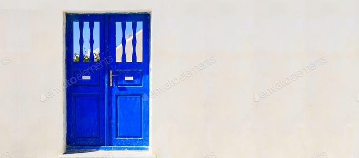 Blue door on a whitewashed wall - Cyclades, Greece
