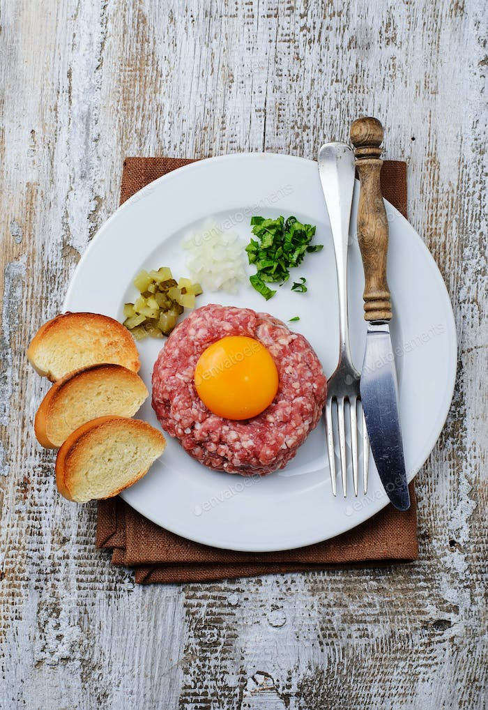 Fresh beef tartar with egg, pickled cucumber and onion.