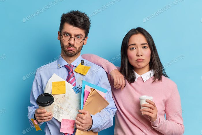 Team work concept. Two displeased tired colleagues prepared financial report together pose with coff