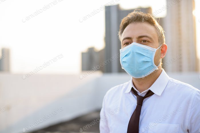 Mature businessman wearing mask for protection from corona virus outbreak and pollution