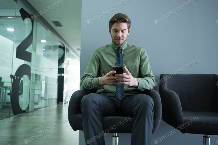 Male executive using mobile phone in waiting area