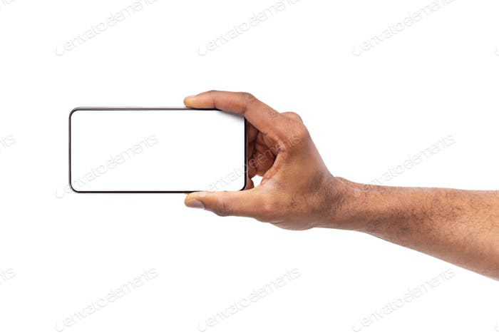 Black male hand holding smartphone with blank screen in horizontal orientation