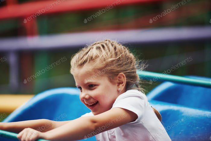 Portrait of happy female kid have fun on a roller coaster in the park at daytime