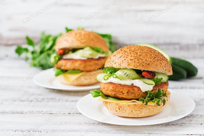 Big sandwich - hamburger with juicy chicken on a light wooden background