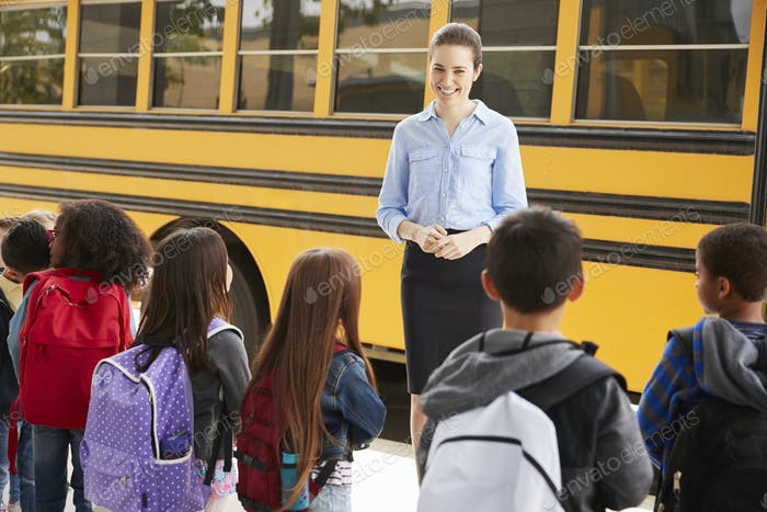 Teacher talking to elementary school kids by school bus