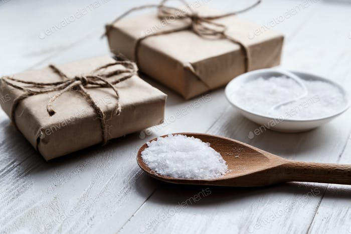 sea salt on wooden background with gift boxes