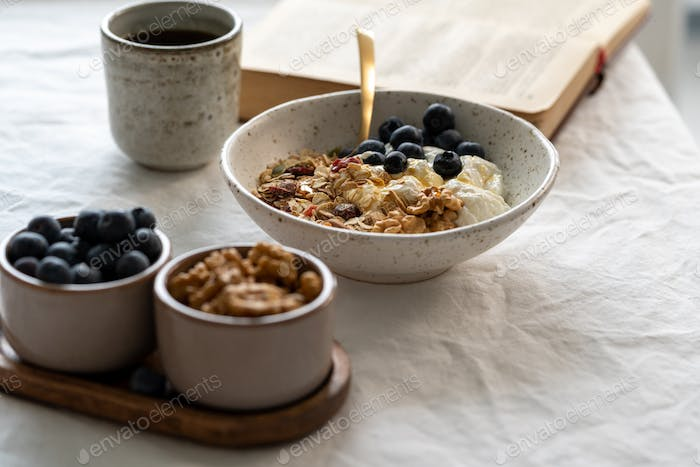 Reading book and eating healthy lifestyle breakfast with granola muesli and yogurt