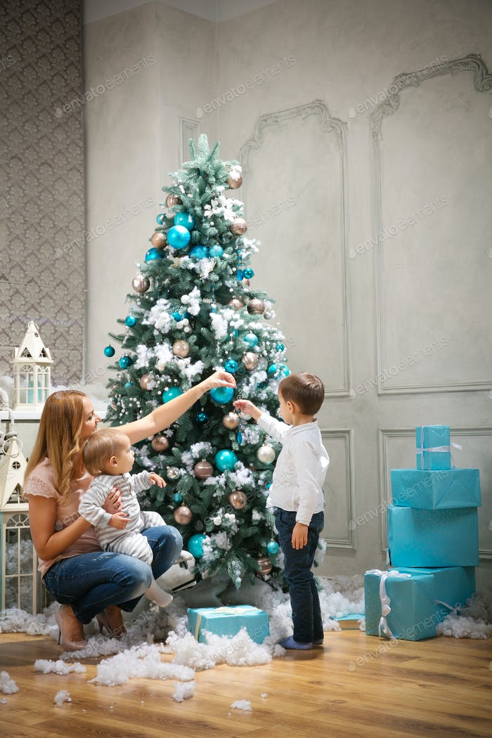 Young woman with two sons decorating on Christmas tree at home