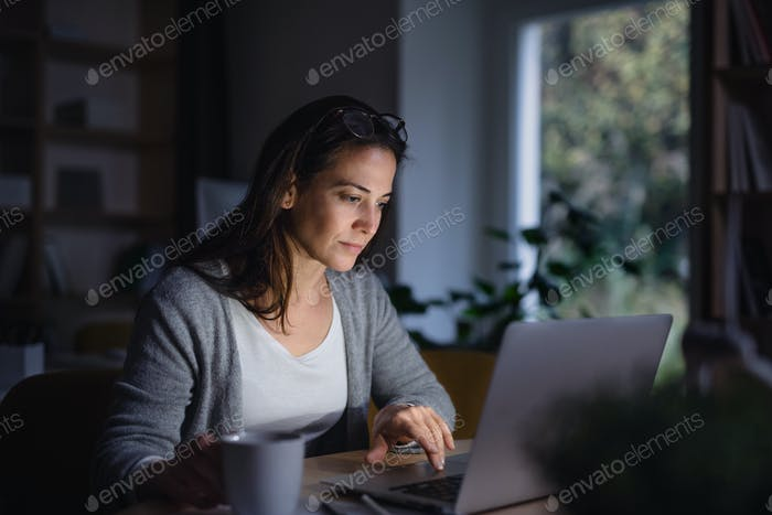 A businesswoman with laptop sitting at the desk indoors in dark office.