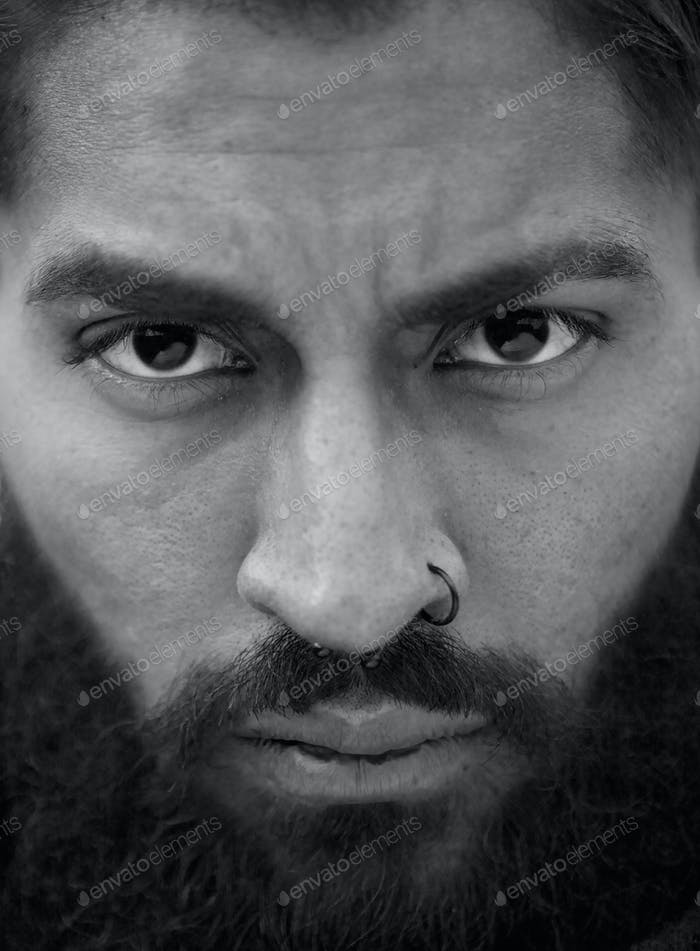 Black and white portrait of man with beard and nose piercing