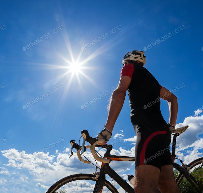 Road cyclist resting on his bike. Backlight, sunny summer day.