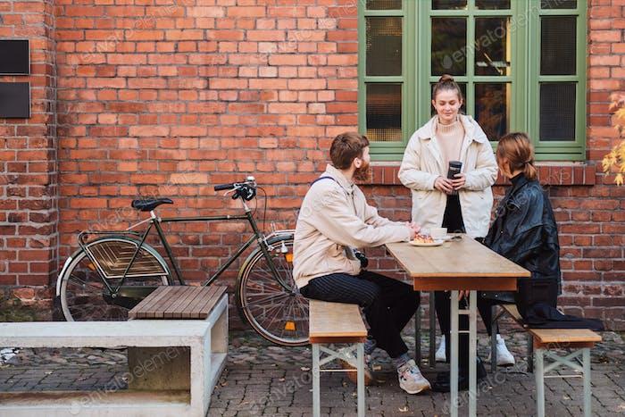 Jóvenes y elegantes amigos felices hablando y bebiendo café descansando juntos en el café en la calle