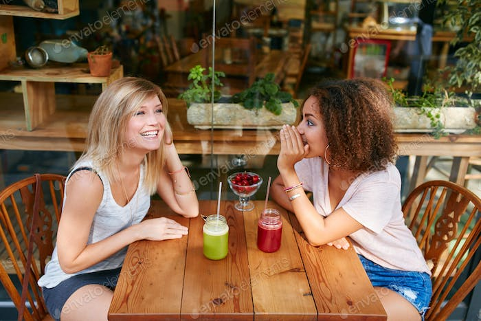 Young female friends having private gossips at cafe