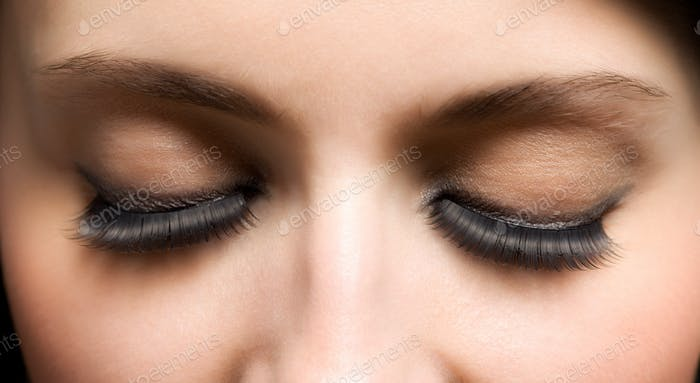 Closed eyes of young womans face with extended lashes