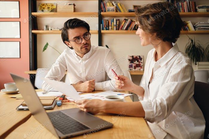 Junge attraktive Geschäftskollegen diskutieren nachdenklich über neue