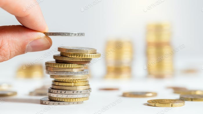 Hand adding a coin on pile of euros with others stacked in background