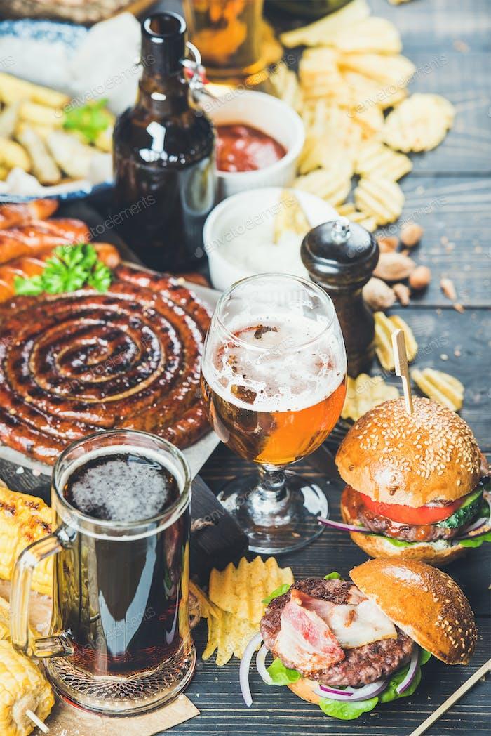 Bier- und Snack-Set auf dunklem Holz verbrannten Hintergrund