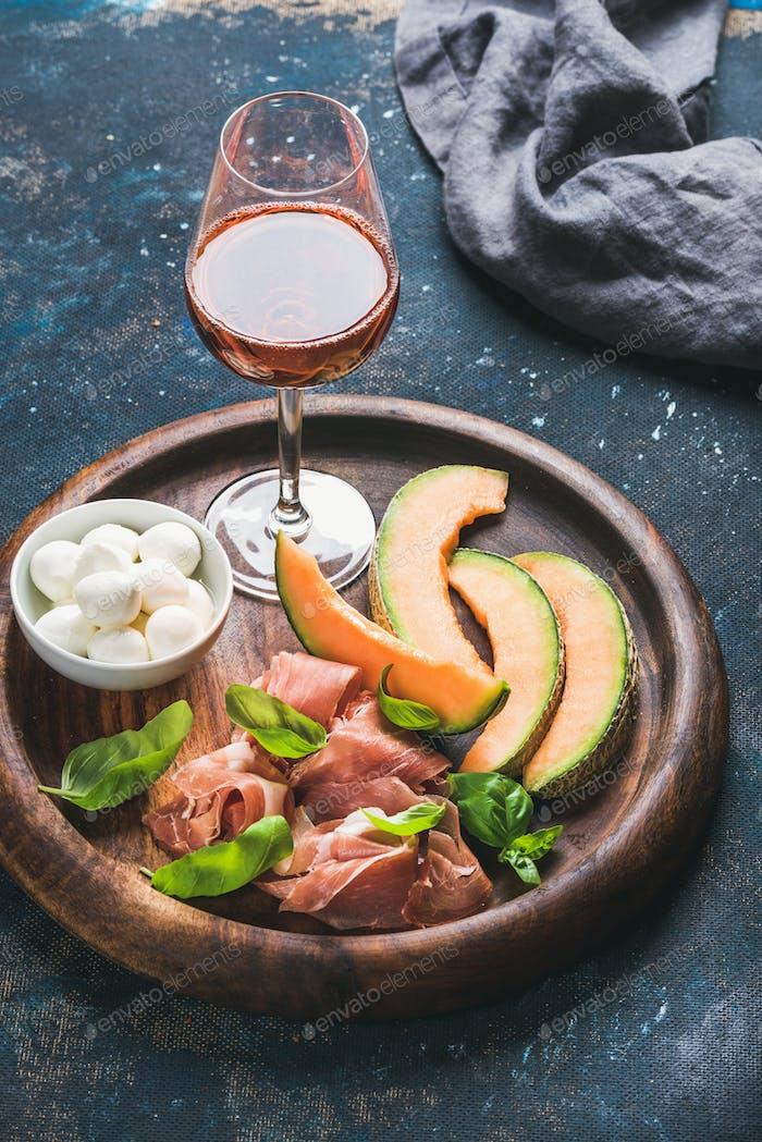 Prosciutto, cantaloupe melon, mozzarella cheese and glass of rose