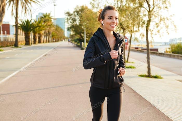 Glückliche junge Sport-Frau Laufen