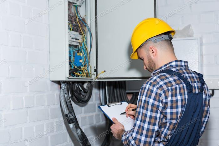 Professioneller Elektriker inspiziert Drähte im Schaltkasten