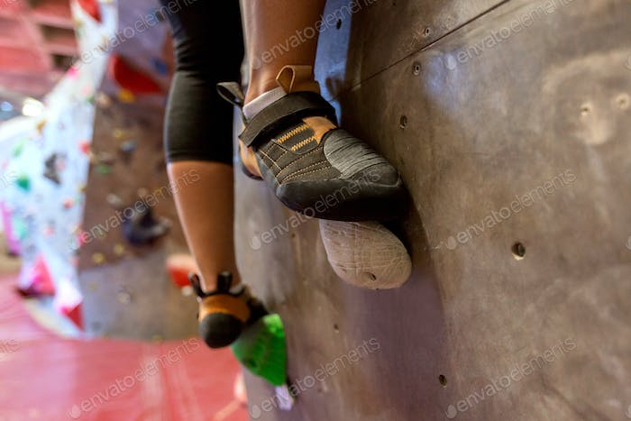 feet of woman exercising at indoor climbing gym
