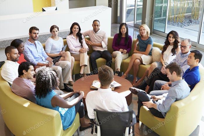 Multikulturelles Büropersonal sitzen mit Treffen zusammen