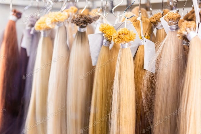 Exhibition of multicolored hair extensions in beauty salon