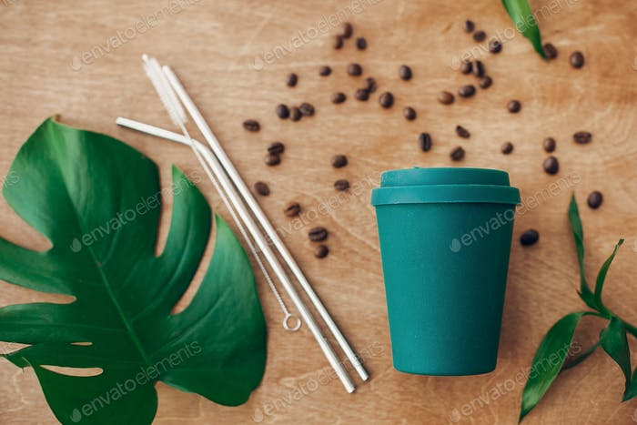 Stylish reusable eco coffee cup  with roasted coffee beans