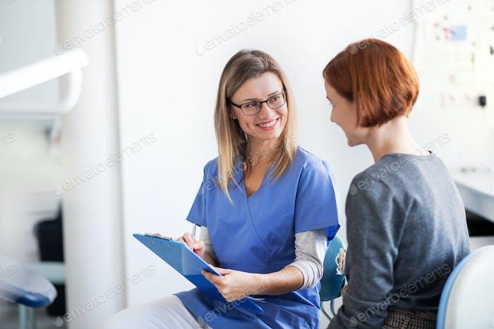 Uma mulher tem um check-up dentário na cirurgia do dentista
