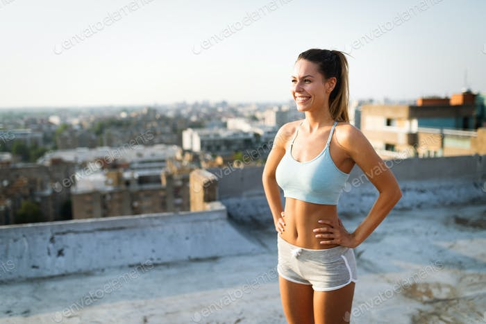 Young attractive fit sporty woman doing workout on the rooftop on sunny day