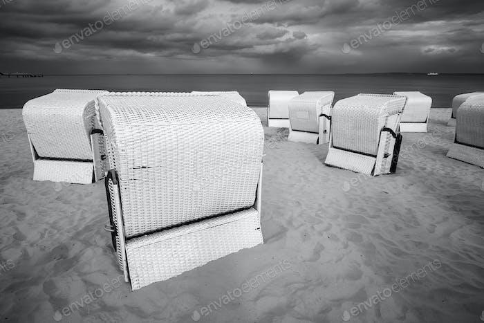 Hooded wicker basket chairs on an empty beach.