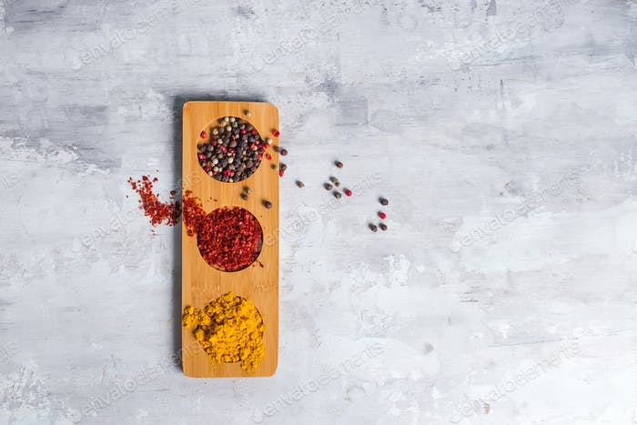 three kind of spices in wooden plate isolated on stone