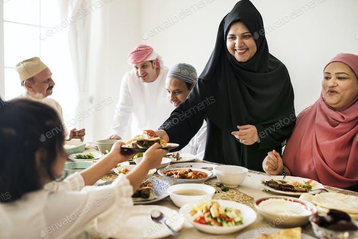 Muslim woman sharing food at Ramadan feast