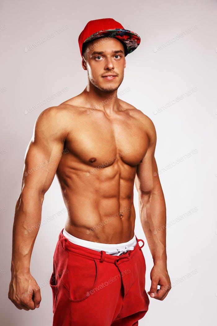 Hombre musculoso en gorra roja.
