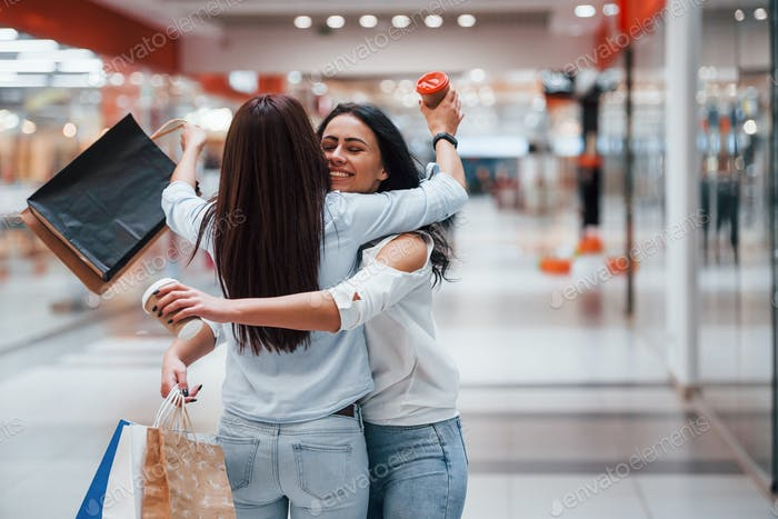 Meeting of two female friends in the mall at weekend shopping time