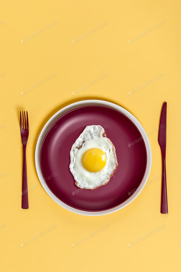 Scrambled eggs on a maroon dish with burgundy cutlery on a light