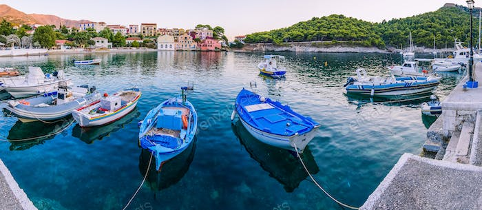 Fisher boats at anchor in the sea bay of Assos village in beautiful azure cove in Kefalonia, Greece