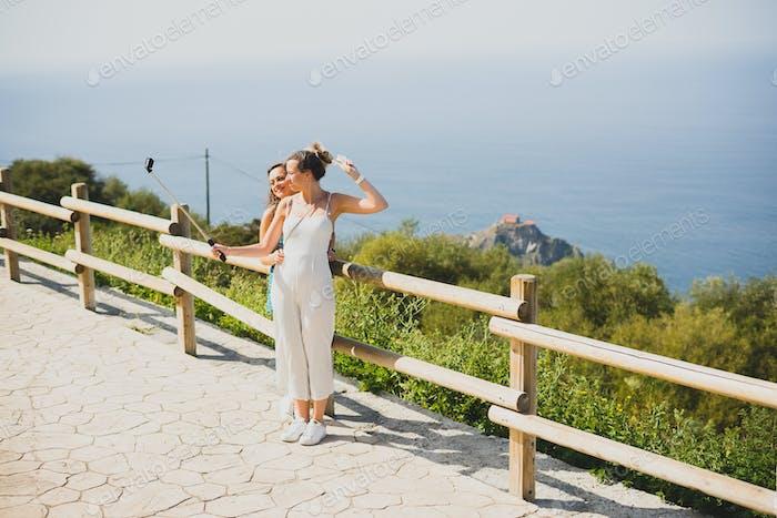 Zwei Schwestern nehmen Selfies mit einem Selfie-Stick mit einer ozeanischen Landschaft hinter sich