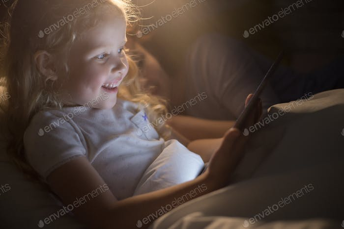 Cute Little Girl Reading E-Book in Bed