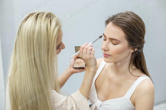 Makeup artist makes makeup to a girl. Apply beige eye shadow. Close-up.
