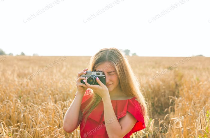 photographer with camera taking picture in the field.