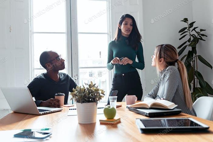 Ziemlich junge Unternehmerin Frau erklärt ein Projekt, um seine Kollegen auf Coworking Platz.