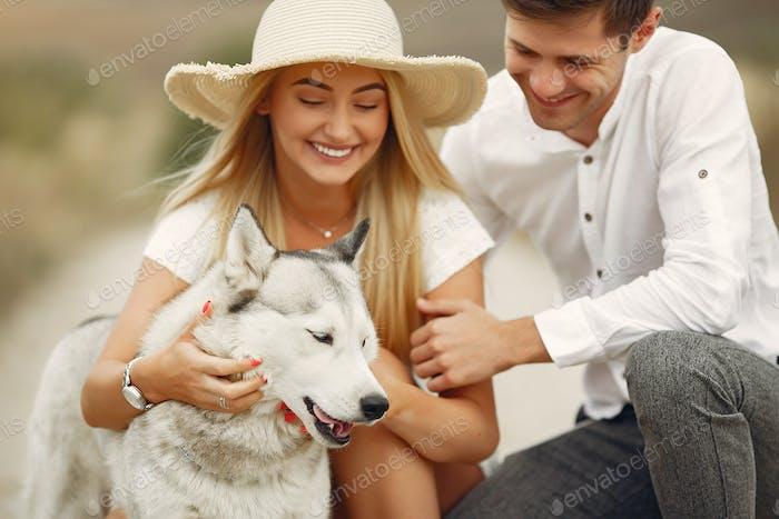 Paar in einem Herbstfeld spielen mit einem Hund