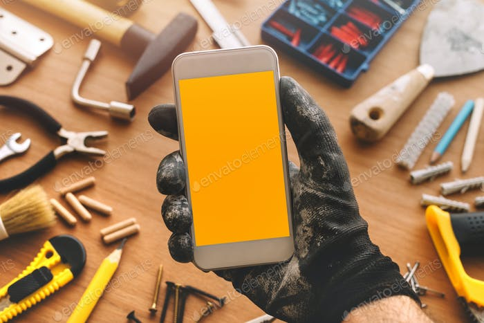 Handyman smart phone app, repairman holding mobile phone in hand