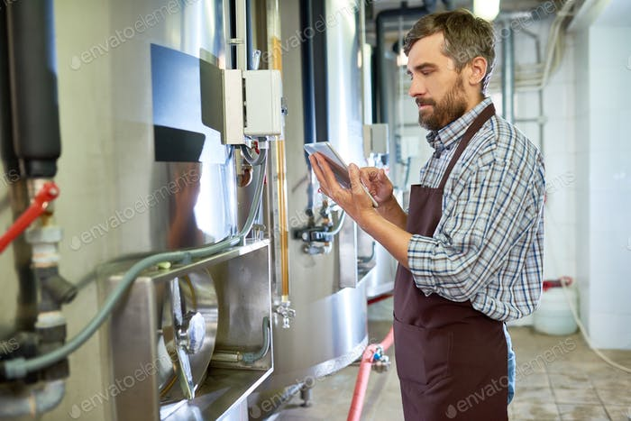 Concentrated beer engineer using tablet while examining equipment